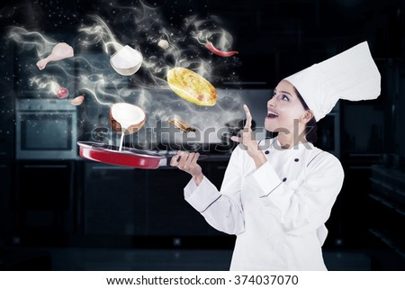 Indian female chef cooking in the kitchen with magic while wearing chef uniform