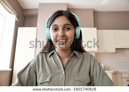 Indian female college student teacher wearing headphones looking at web cam distance learn or teach online. Web lesson video call remote class, online job interview concept. Headshot. Webcam view.