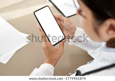 Indian female doctor holding in hands using cell phone app mock up white screen, over shoulder closeup view. Healthcare telemedicine online consultation, remote mobile medical smartphone application