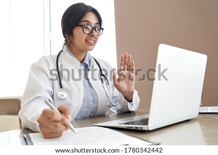 Indian female doctor talk with patient make telemedicine online webcam video call. Female physician therapist videoconferencing on computer in remote telemedicine laptop virtual chat. Telehealth.