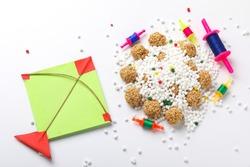 indian festival makar sankranti concept : sesame seed ball or til ke laddo and tilgul in bowl and colorful paper kite on white background