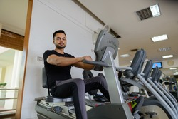 Indian fitness man using exercise bicycle