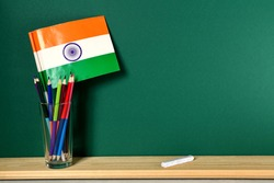 Indian flag in a glass with pencils and white chalk on the background of the training board with space for text on the right. Educational background.