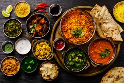 Indian food Curry butter chicken, Palak Paneer, Chiken Tikka, Biryani, Vegetable Curry, Papad, Dal, Palak Sabji, Jira Alu, Rice with Saffron on dark background