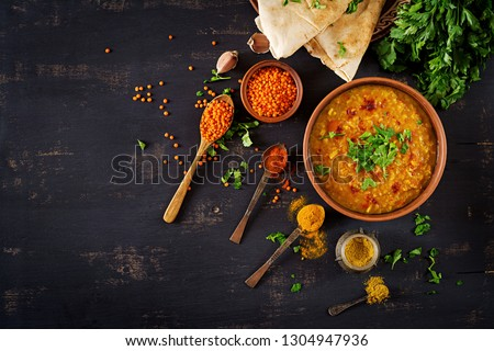 Indian food dal. Traditional Indian soup lentils.  Indian Dhal spicy curry in bowl, spices, herbs, rustic black wooden background. Top view.  Authentic Indian dish. Overhead. Flat lay