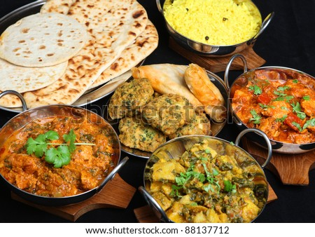 Indian food with curries, rice, naan bread, samosas and pakora.