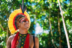 Indian from the Pataxó tribe with feather headdress looking to the right. Indigenous from Brazil with traditional facial paintings.
