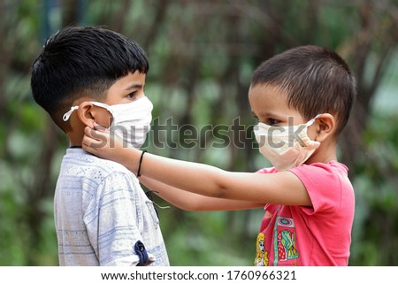 Indian girl helping brother wearing face mask to prevent covid-19. sister taking care of brother during corona virus pandemic. Teaching to wear mask properly. How to wear face mask.
