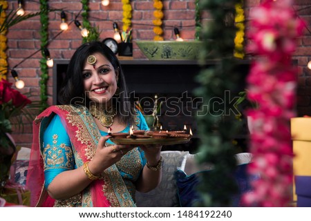 Indian girl holding diwali diya in traditional wear, clicking selfie picture or speaking over smartphone.