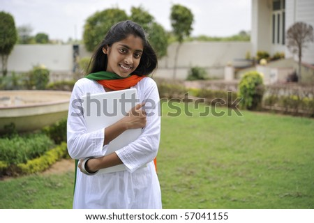indian girl holding laptop outdoors