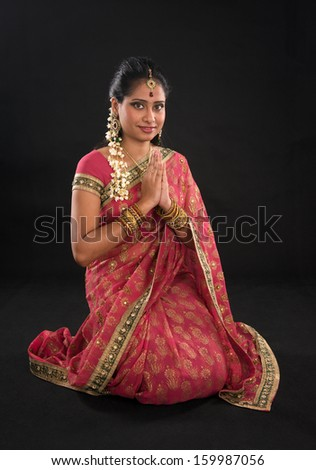 Indian girl in a greeting pose, traditional sari costume, full length kneeling on floor isolated on black background