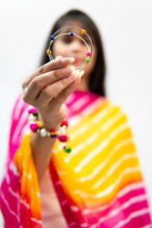 Indian girl in traditional Indian dress (Salwar Kameez, dupatta) standing against white isolated background showing bangles to the camera.