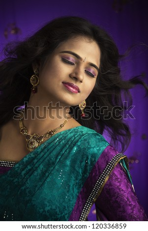 Indian girl in traditional Indian sari posing to the camera.