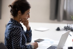 Indian girl sitting at desk near computer cogitating thinking making important decision at workplace. Concentrated serious office worker millennial woman analysing results feels doubts and feel unsure