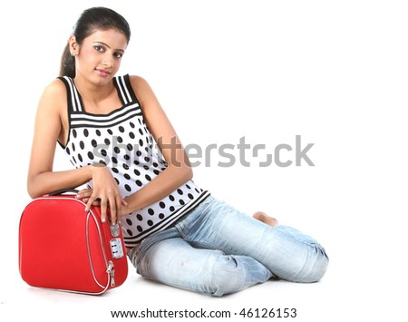 indian Girl sitting near a suitcase