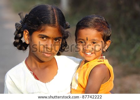 Indian girl with little boy in outdoor background. - stock photo