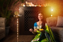 Indian Girl / women holding Pooja Thali while wearing green saree and sitting at home with flower rangoli and Samai, celebrating Diwali or hindu festival. selective focus