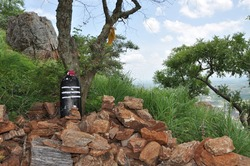 Indian god, lord Siva statue situated among the rocks.