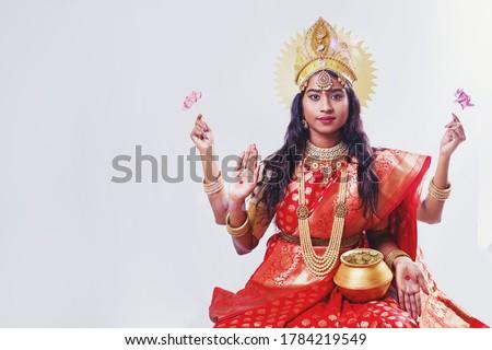 Indian Goddess Lakshmi. Woman in Lakshmi costume looking at camera over white background. Diwali, Vaibhavalakshmi celebrations concept. Stock photo ©