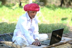 Indian grandpa happy to use laptop. Indian old farmer smiles using laptop and internet. Farmer loves technology, Old farmer works on Laptop. Indian sitting on Cot. Cot in Farm. Smile of Knowledge.