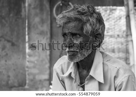 Indian grey-haired old man with beard looking thoughtful in Mysore, Karnataka, India. Black and white photography. Poor man with sad, concerned expression