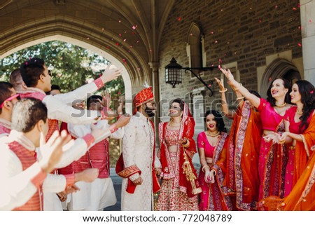 Indian groom dressed in white Sherwani and red hat with stunning bride in red lehenga pose with their groomsmen and bridesmaids outside