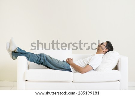 Shutterstock Indian guy daydreaming and rest at home. Asian man relaxed and sleep on sofa indoor. Handsome male model.