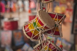 Indian Hand Drums - Damroo, hanging for sale on shop front in Trimbak, Maharashtra. Religious city in India around Trimbakeshwar Temple. Damroo is the musical instrument of Lord Shiva.