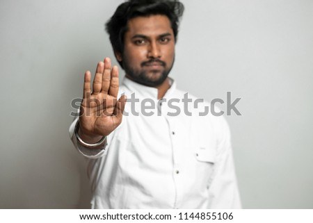 indian handsome man showing 'no' gesture. stop keep calm. watch out. mesmerizig process. hipnotize people. indian hypnosis. stop drinking alcohol, smoking