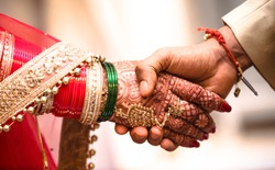 Indian Hindu Couple holding each other hands during their marriage symbolising love and affection. Hands of bride is decorated beautifully by indian mehndi art alongwith jewellery and colorful bangles