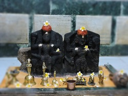 indian hindu god and goddess made from black stone sculpture kept in a temple of holy sacred village in Maharashtra. bells instruments in front made with bronze and gold decorated with white flowers