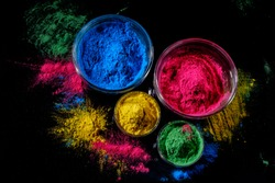 Indian Holi festival colours (colorful gulal) in four bowls on dark background.