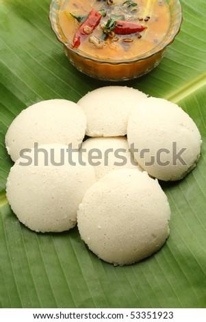 Indian idli with sambar on a banana leaf - stock photo