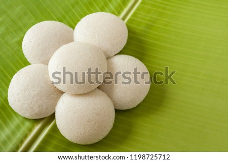 Indian idly served as a flower - Fresh steamed Indian Idly (Idli / rice cake) arranged decoratively as a flower on traditional banana leaf. Natural light used.