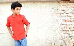 Indian kid standing outside against wall