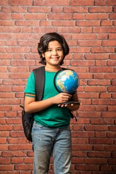 Indian kid with educational globe, isolated on red brick wall. Curious male child holding earth round model in his hand. Little traveler, exploring new horizons