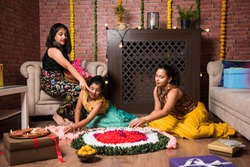 Indian Kids celebrating Diwali / Deepawali, Bhai Dooj or Rakhi / Raksha Bandhan with flower rangoli, gifts, diya