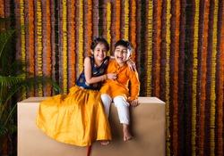 Indian kids, little brother and sister celebrating Diwali, Raksha Bandhan, Bhai Dooj with big gift box and sweet laddoo