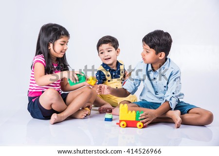 indian kids playing with block toys, asian small kids playing indoor games, colorful plastic block toys, making toy house, over white background, indian small girl and indian small boy playing blocks