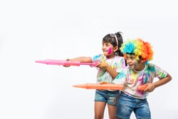 indian kids playing with colours or asian children celebrating holi - festival of colours