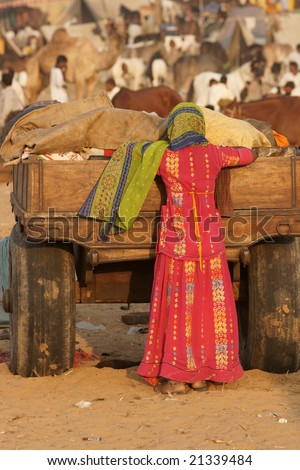 Indian lady in brightly colored clothing next to a camel cart at the Pushkar Fair in Rajasthan, India