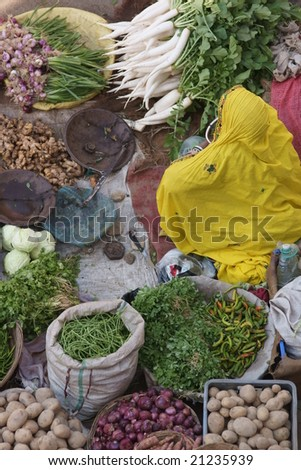 Indian lady in yellow sari selling fruit and veg at a street market in Pushkar, Rajasthan, India