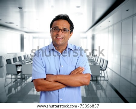 indian latin businessman glasses blue shirt in boardroom office [Photo Illustration]