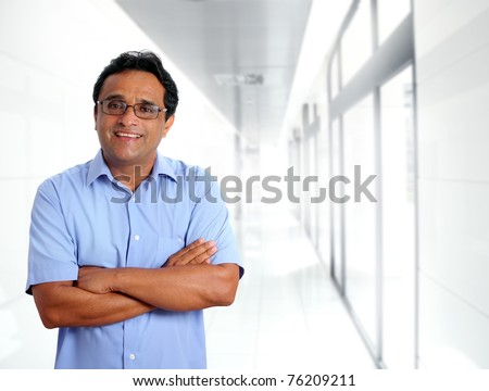 indian latin businessman glasses blue shirt in modern office corridor [Photo Illustration]