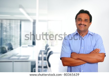 Indian latin businessman with blue shirt in modern office background [Photo Illustration]