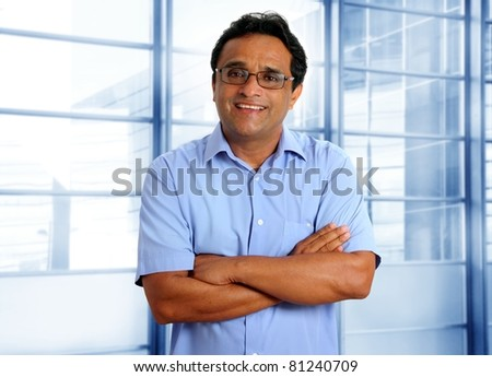 indian latin businessman with glasses and blue shirt in modern office [Photo Illustration]