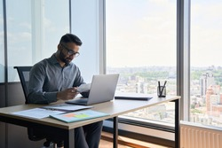 Indian latin focused financier sitting at desk doing paperwork working with bank taxes, loans, debit, credit operations using laptop near panoramic window in contemporary corporation office.