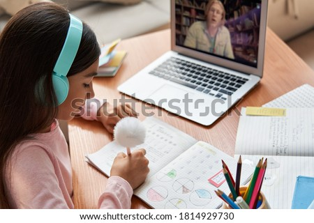 Indian latin preteen girl school pupil wearing headphones distance learning online at virtual lesson with math teacher tutor on laptop screen by video conference call at home. Over shoulder view.