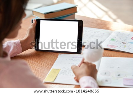 Indian latin school girl student distance learning, studying online at home, elearning, watching webinar, web class holding digital tablet. Virtual education. Over shoulder close mock up screen view.