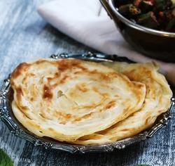 Indian layered paratha served with bhindi masala, selective focus